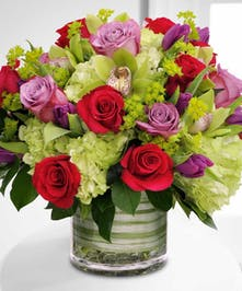 his arrangement is composed of hydrangea, fragrant roses, seasonal tulips and cymbidium orchids sitting inside a cylinder glassed vase.