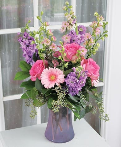 Pink roses and daisies with lavedner stock in a lavender vase