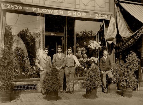 A vintage photo of Thomas Kegan and staff outside the original Blossom Flowers, circa 1925